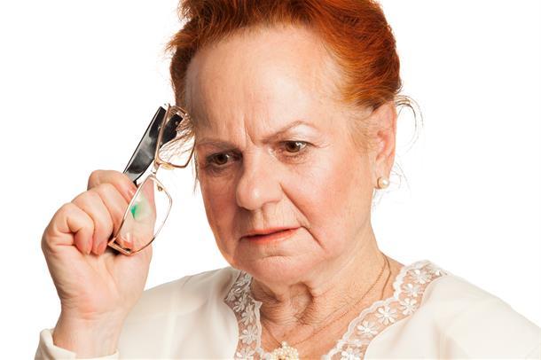 Kvinne holder brillene mot pannen og tenker hardt. Foto.