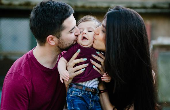 Et ungt par omfavner et barn. Foto.