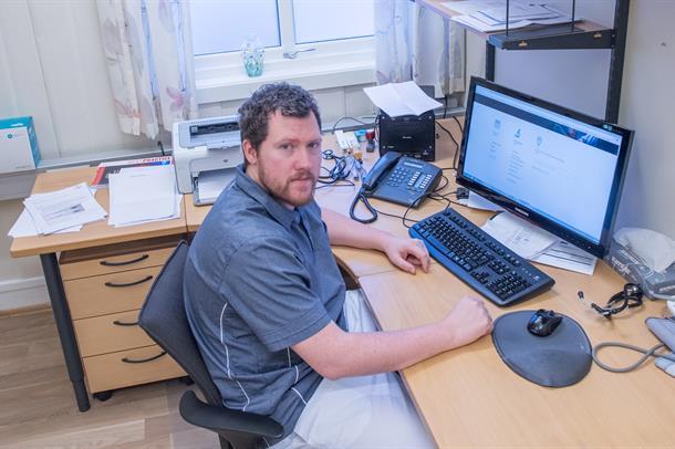 Fastlege Steffen Krogh Vadseth ved sin kontorpult. Foto.