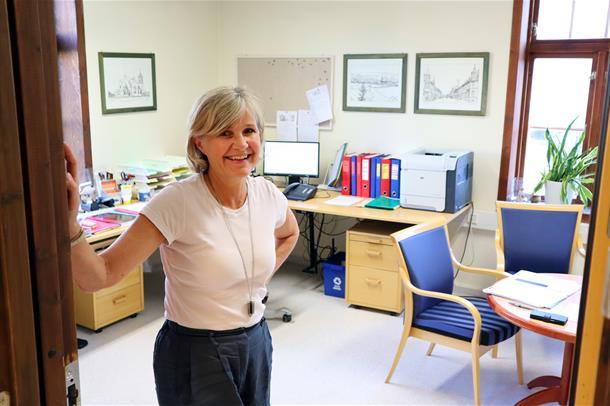 Bine-Kristin Kristoffersen står i døråpningen til sitt eget kontor og smiler til kamera. Foto.