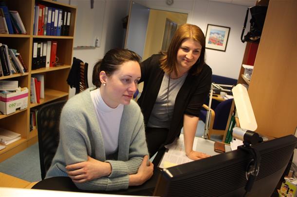 Ingunn Bosnes og Hege Rasmussen Eid står sammen ved en datamaskin. Foto