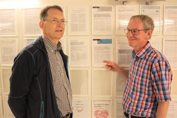 Forskerne Ole Bosnes og Eystein Stordal står og peker på en av mange forskningsartikler på en vegg. Foto