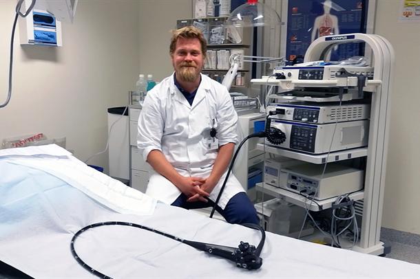 Eivind Ness-Jensen sitter med hvit frakk på en stol ved en behandlingsbenk. Foto.