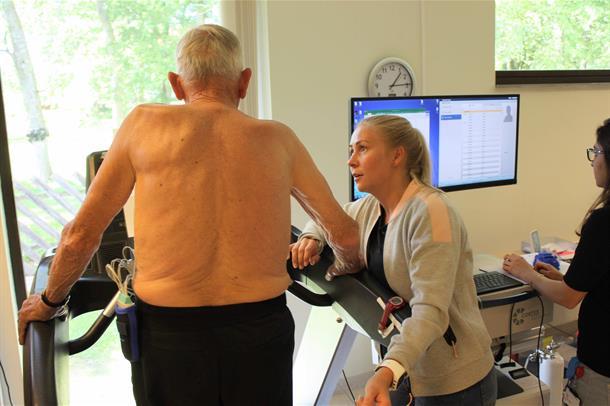 Lisbeth Røe fra HUNT4 Kondisjonsprosjektet står ved en tredemølle og instruerer deltaker Lars Myhre. Foto