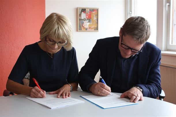 Bodil Landstad og Göran Larsson sitter ved et bord og signerer intensjonsavtalen. Foto