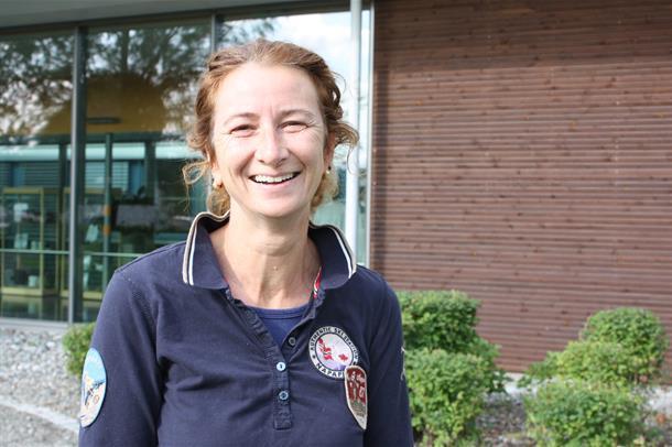 Sara Germans Selvik står utendørs foran en glassgang og smiler til kamera. Foto.