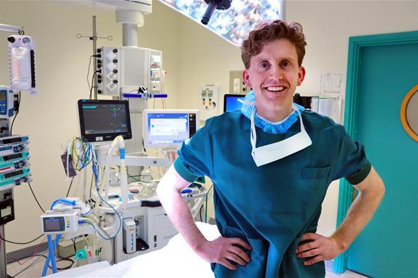 Anders Hynne sitter på en operasjonsseng og ser i kamera. Foto
