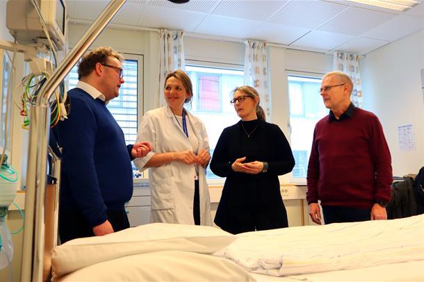 Petter Tinbod Eggen, Nina Vibeche Skei, Inger-Lise Bangstad og Malvin Torsvik står sammen og snakker ved en pasientseng. Foto