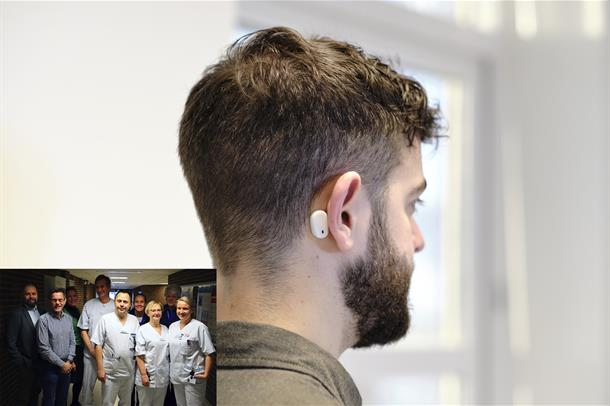En mann står med ryggent il kamera, med en liten, hvit sensor plassert bak øret. Foto