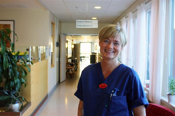 Fysioterapeut Kathrine Engen står i foajeen ved avdelingen sin og smiler til kamera. Foto