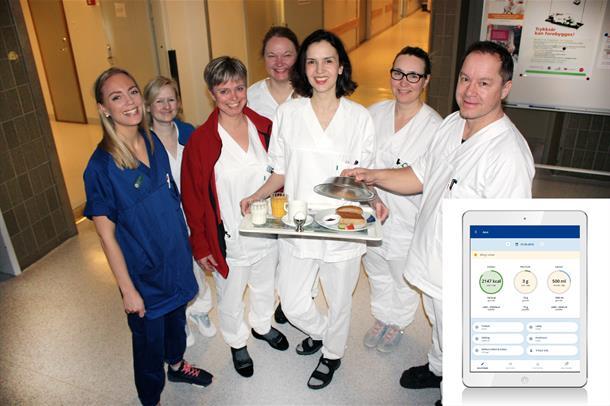 Flere helsearbeidere står rundt en person som holder et brett med mat. Foto