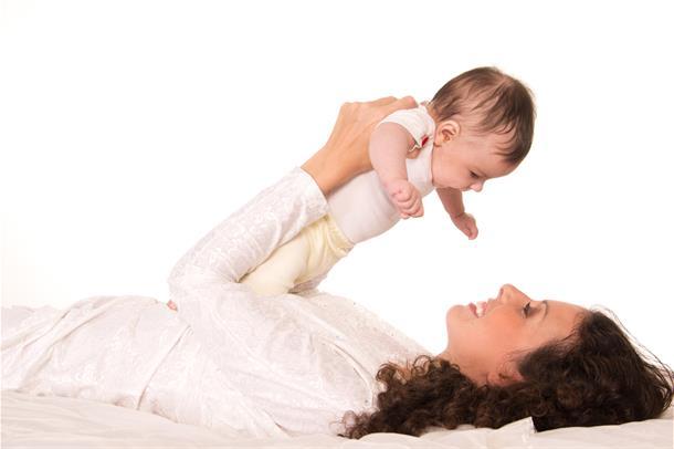 Kvinne ligger i en seng og holder barnet sitt over sitt eget ansikt. Foto