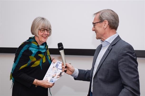 Administrerende direktør Lars Vorland i Helse Nord RHF overrekker rapporten til statssekretær Anne Grethe Erlandsen. Foto