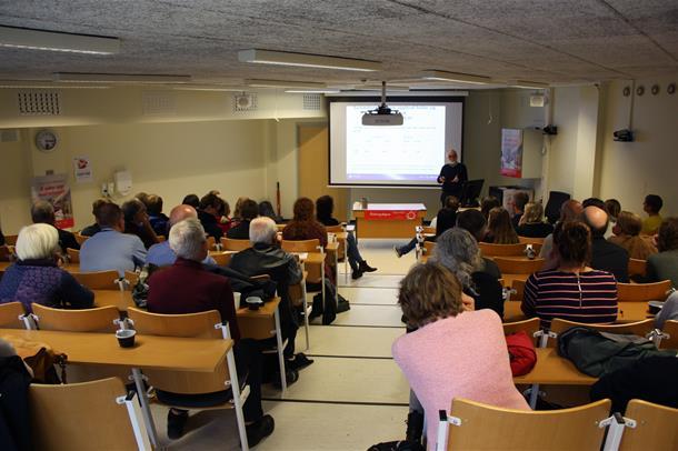 Bilde tatt bakerst i salen av forsker Arve Strandheim som holder foredrag for publikum. Foto.