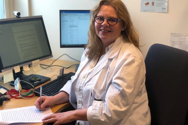 Forsker Siren Nymo sitter ved kontorpulten og smiler til kamera. Foto.