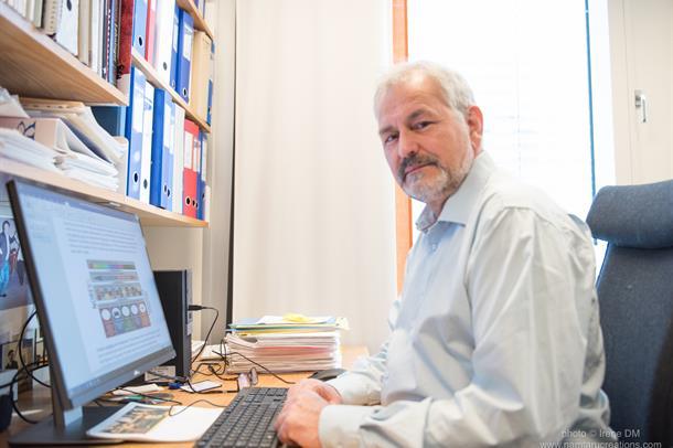 Oluf Dimitri Røe sitter ved en kontorpult og ser i kamera. Foto.