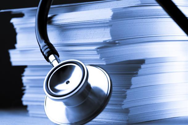 Stetoskop og en bunke dokumenter. Foto.